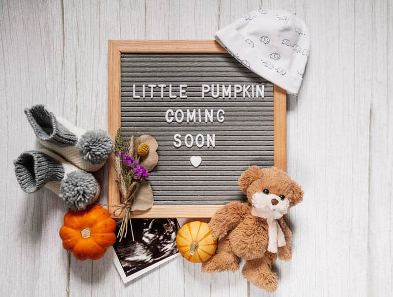 Baby announcement sign on a rustic white table with baby items