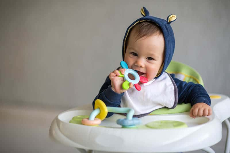 Baby boy chewing toy while sitting in walker