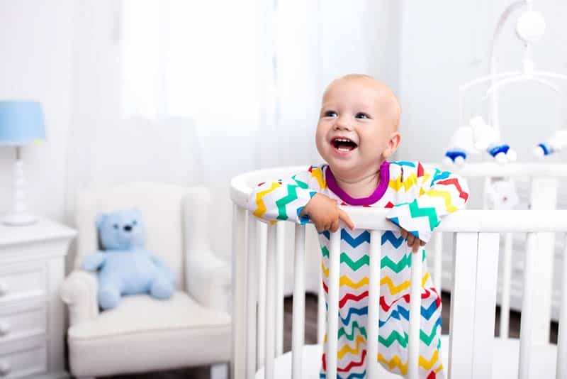Cute laughing baby standing in bed after nap time