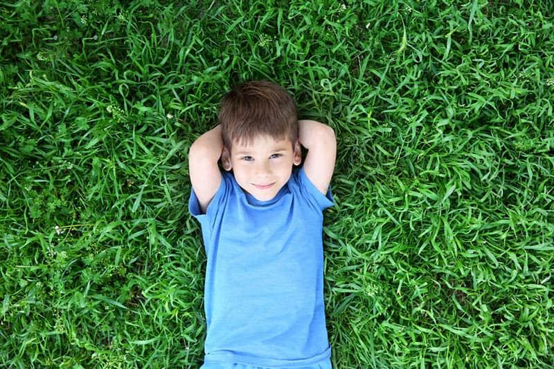 Cute little boy lying on green grass in park
