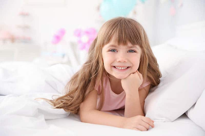 Cute little girl lying in bed at home