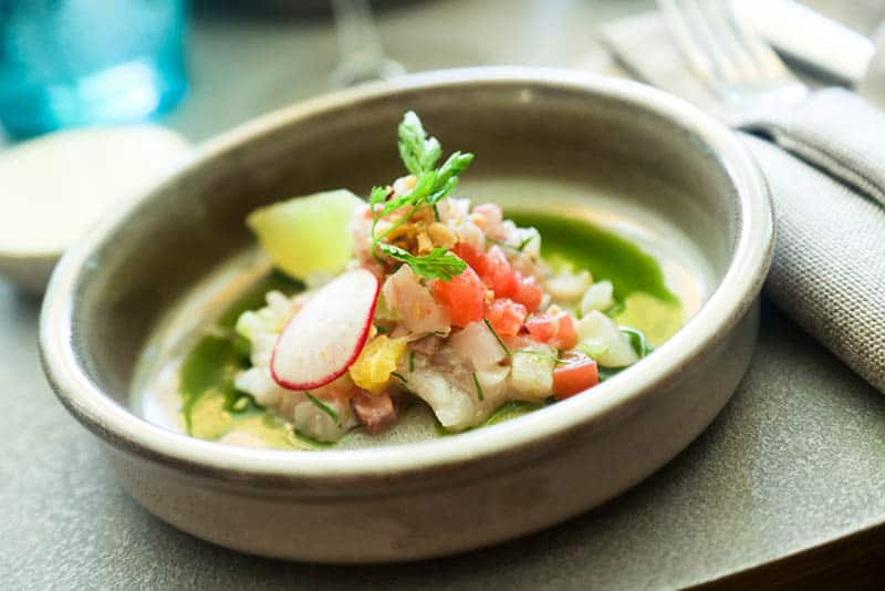 Fish ceviche served with green sauce and lime