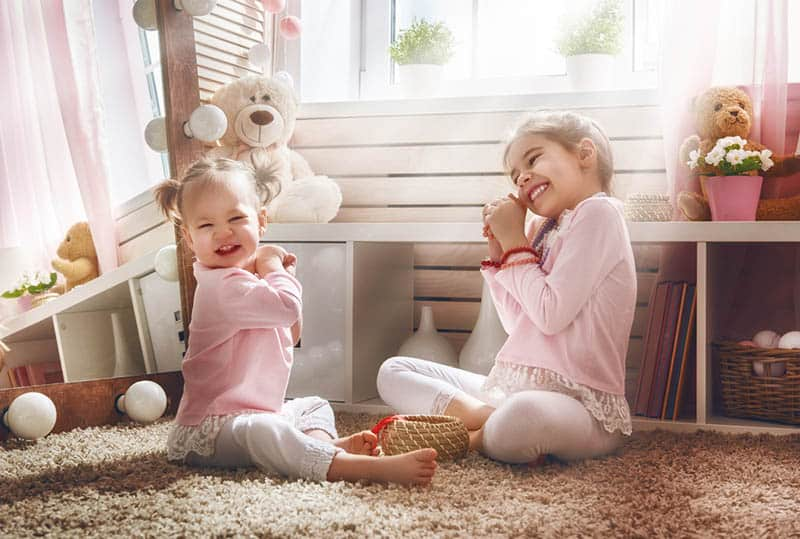 Funny lovely sisters are having fun in kids room