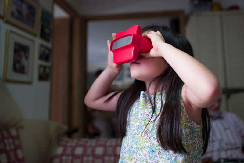 Girl looking through stereoscopic Viewfinder toy