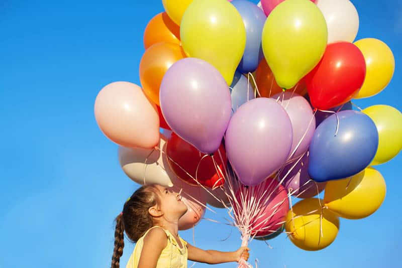 Happy little girl holding colorful balloons outdoors