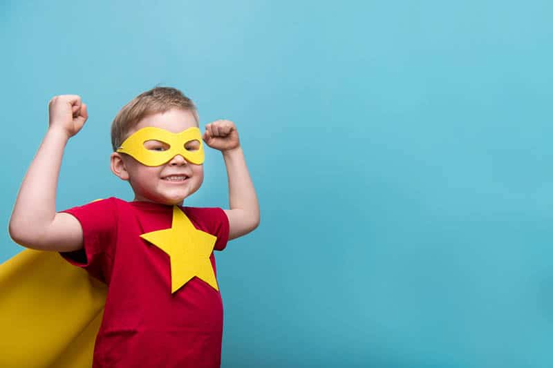 Little child dressed up as a superhero with yellow cloak and star