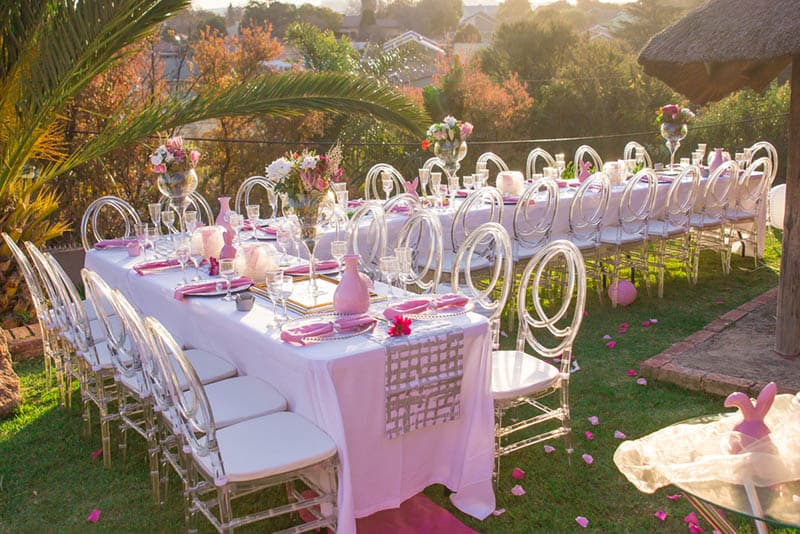 Party tables and chairs seating with pink decorations for a baby shower