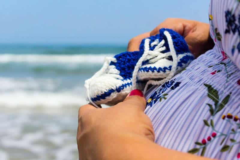 Pregnant Woman holding a pair of baby crochet sneakers on belly
