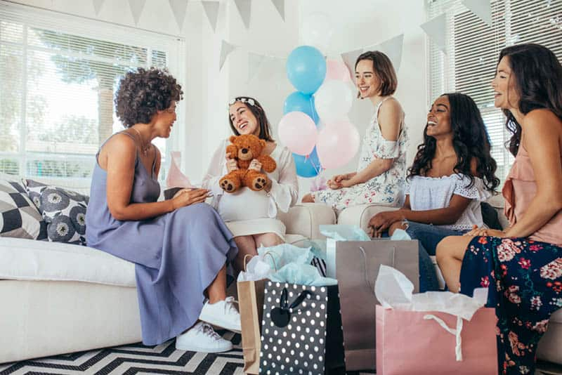 Pregnant woman celebrating baby shower party with friends