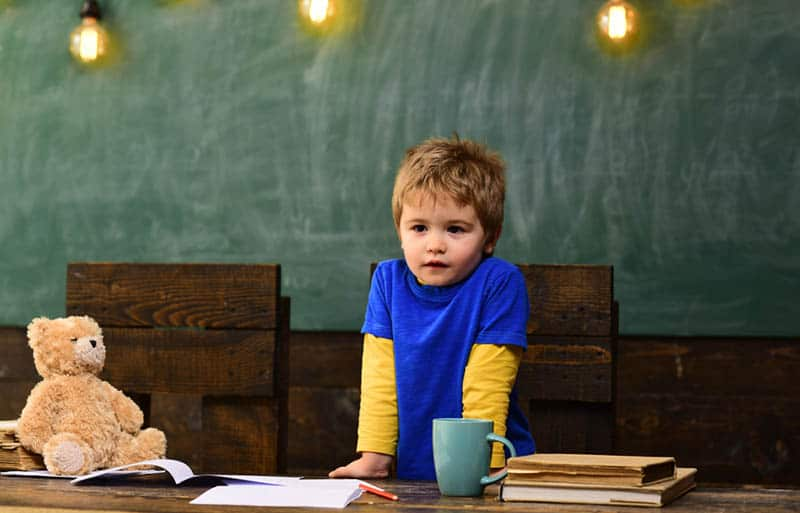 Small boy with serious face standing behind dark wooden table