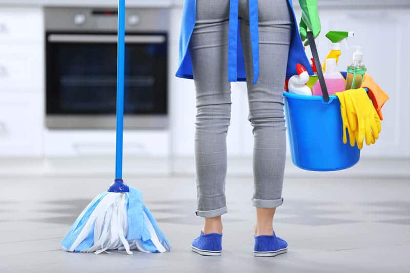 Woman with floor mop and bucket with washing fluids