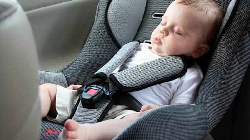 adorable baby boy sleeping in a car seat