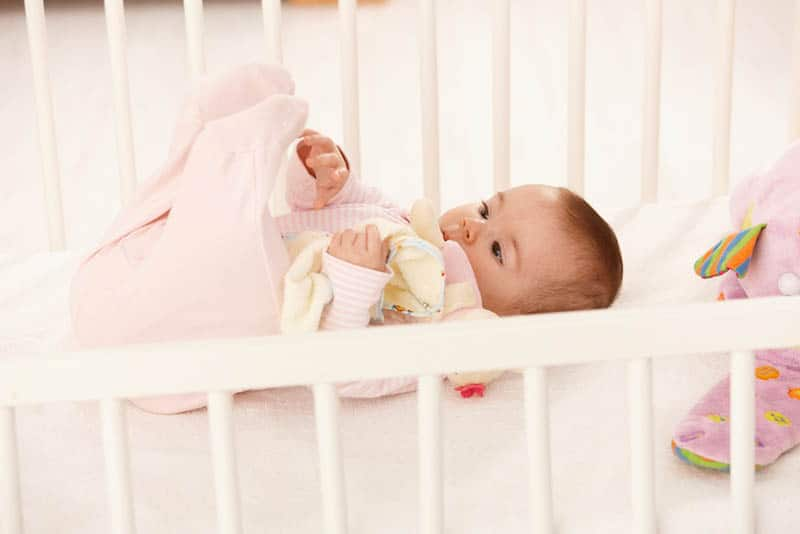adorable baby girl playing with her foot in the crib