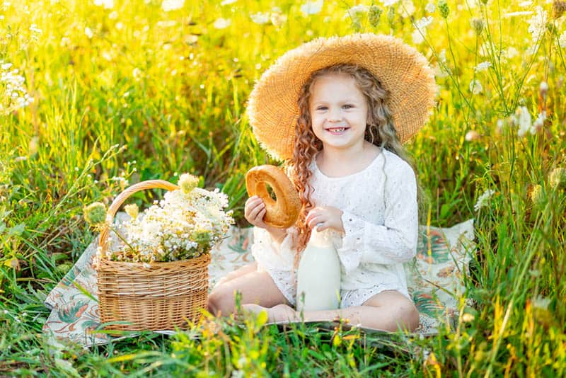 adorable little girl sitting in the field with flower basket