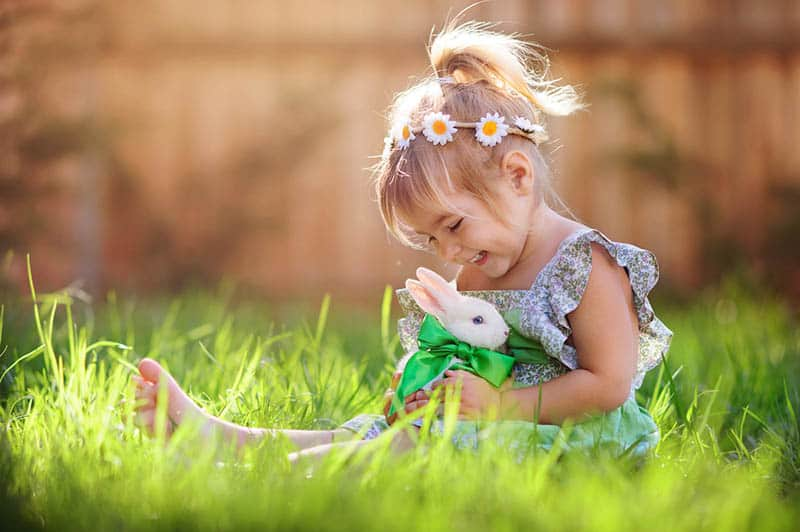 adorable little girl sitting on grass with bunny rabbit