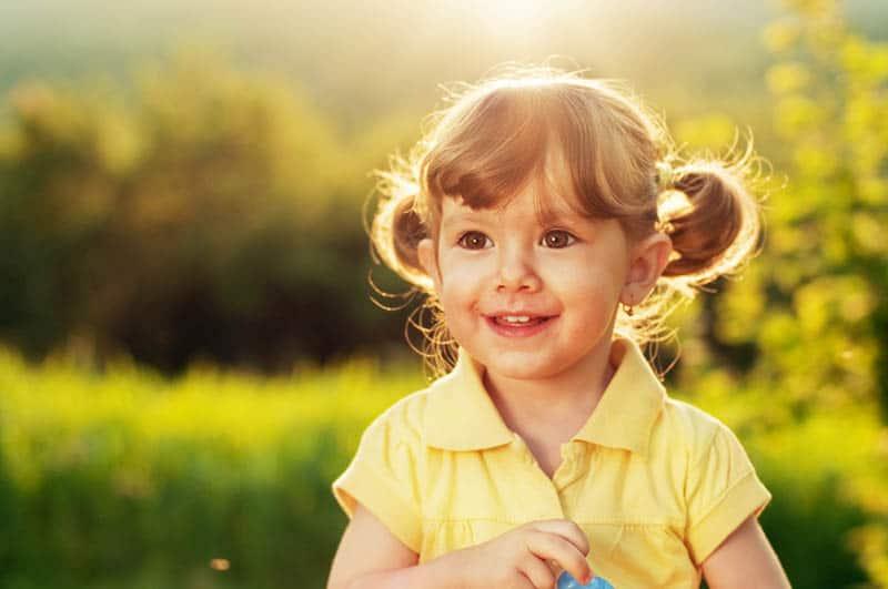 adorable little girl standing in sunlight outdoor