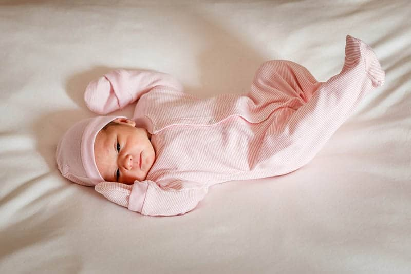 baby girl wearing onesie with hat and gloves lying on bed