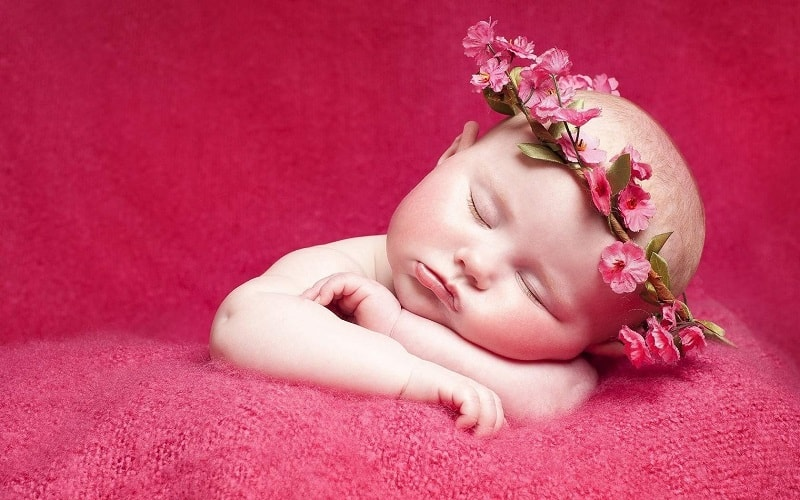 baby girl sleeping while wearing a flower crown