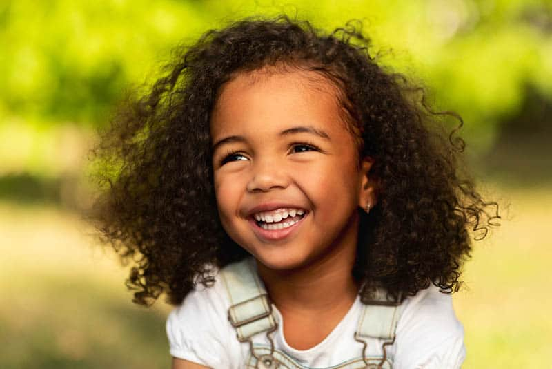 beautiful little girl with curly hair laughing outdoor