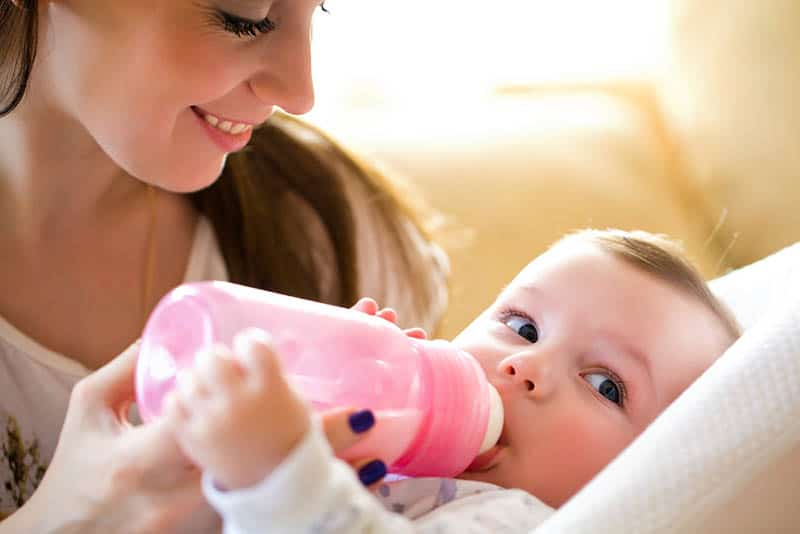 beautiful mother feeding her baby with milk bottle
