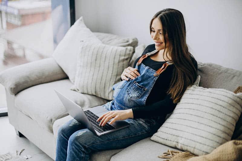 beautiful pregnant woman using computer at home