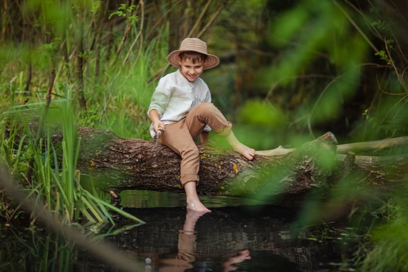 boy in rustic clothes and wicker hat