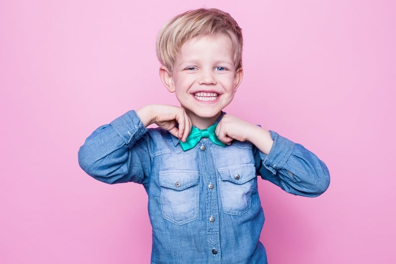 boy wearing a blue shirt and bowtie posing in front of a pink background