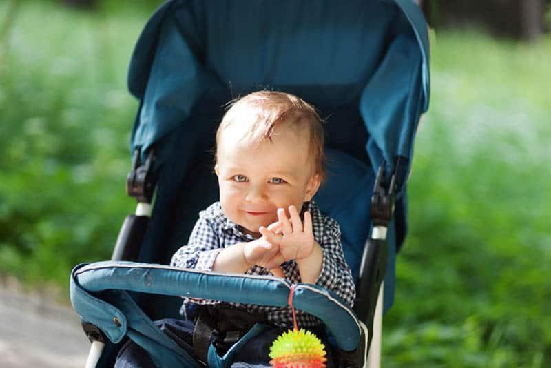 cute baby boy sitting in a stroller in the park