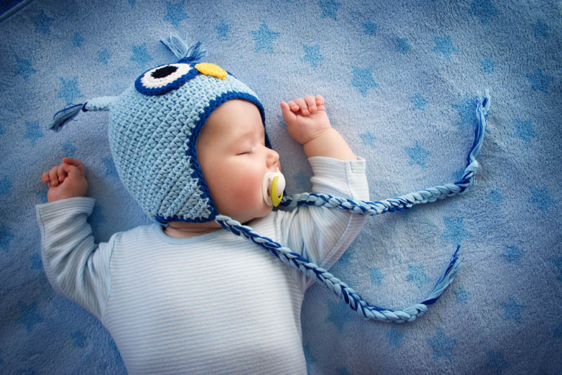 cute baby boy with winter hat sleeping on the blue blanket