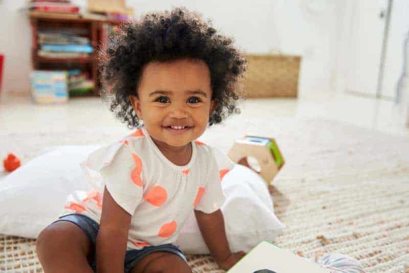cute baby girl with curly hair smiling
