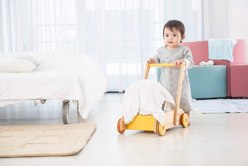 cute baby walking with push walker at home
