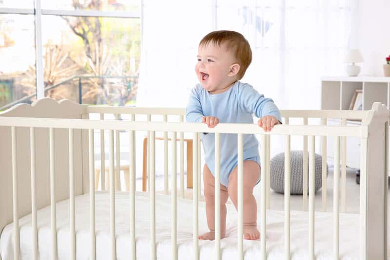 cute happy baby boy standing in the crib holding for rails