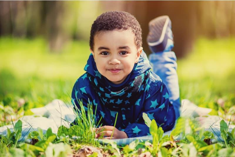 cute happy little boy lying on green grass on spring