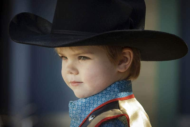cute kid dressed like a cowboy standing outdoor