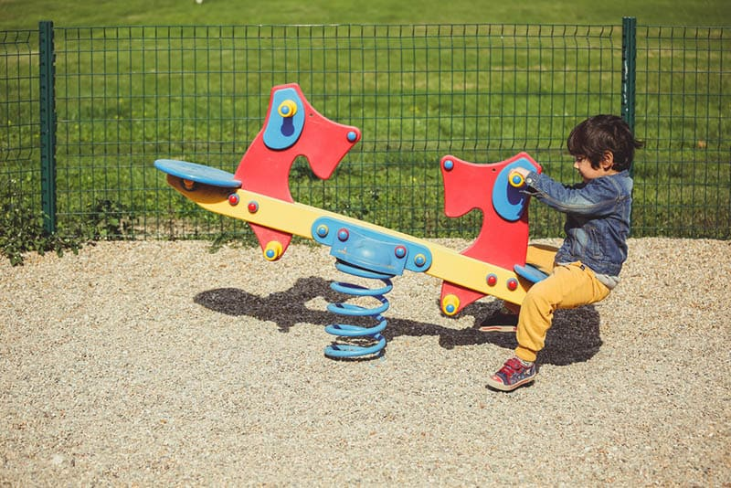 cute little boy playing on a seesaw at the playground
