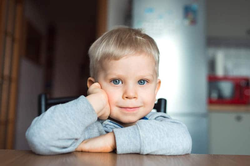 cute little boy sitting on chair in the kitchen