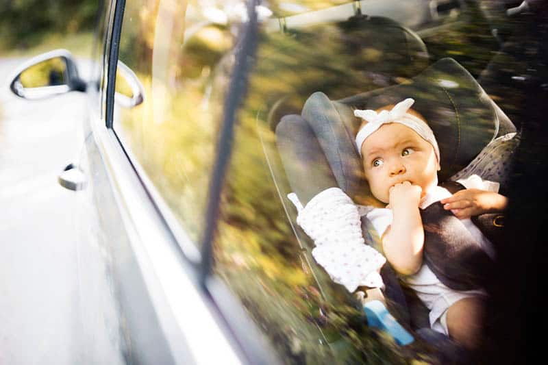 cute little girl driving in a car while sitting in a car seat
