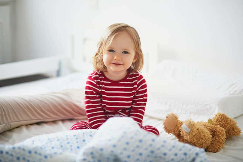 cute little girl in pajama sitting in her bed and smiling