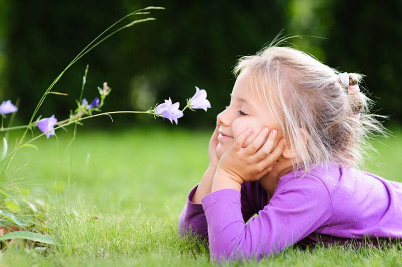 cute little girl lying in the garden and looking at a wild flower