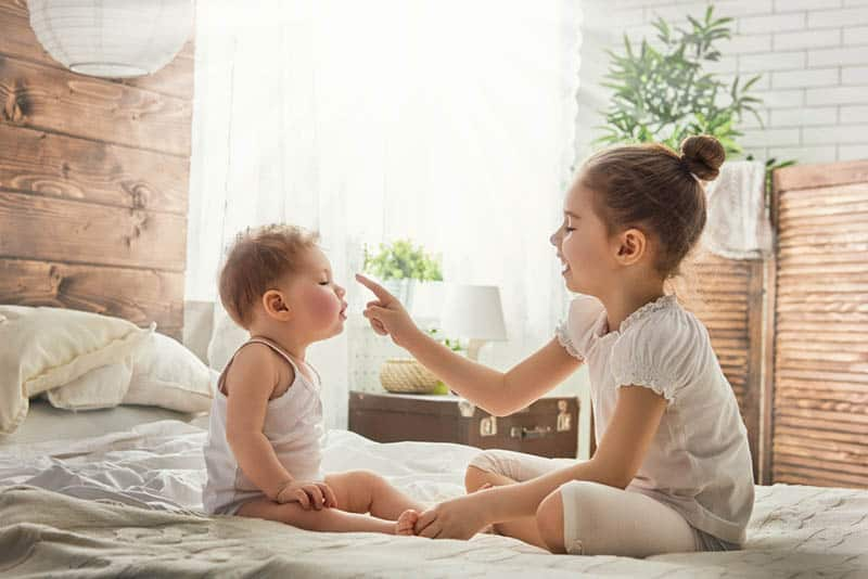 cute little girl playing with her baby brother on the bed
