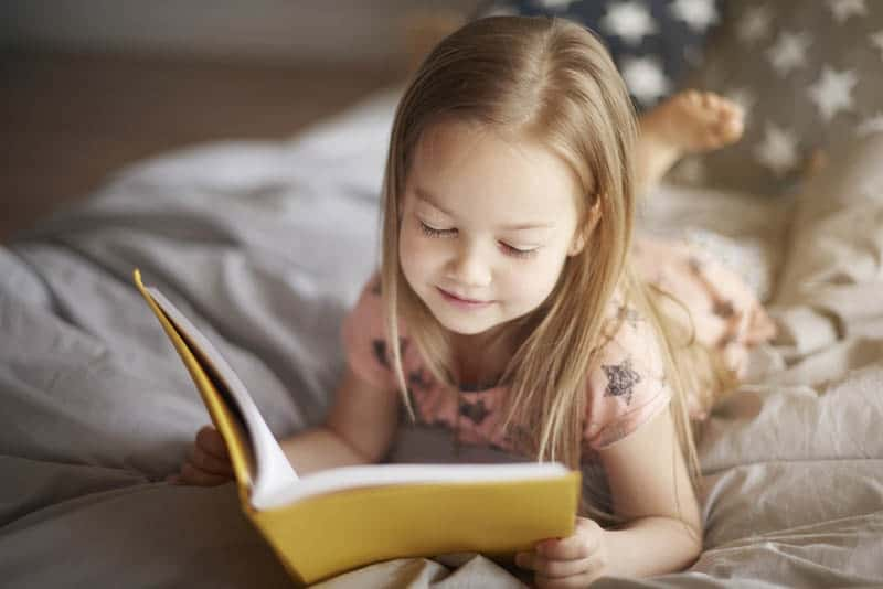 cute little girl reading a book in bed
