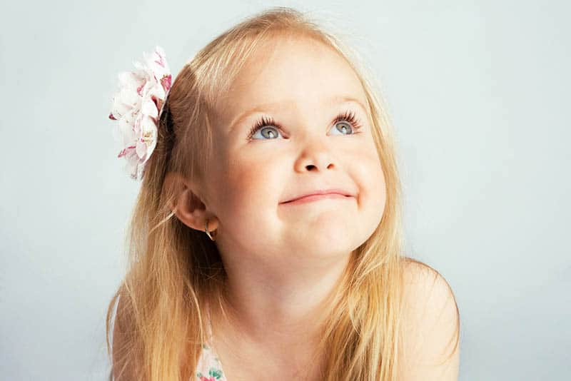 cute little girl with flower in her hair smiling and looking up