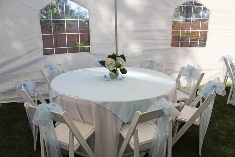 decorated table with chairs in a white tent
