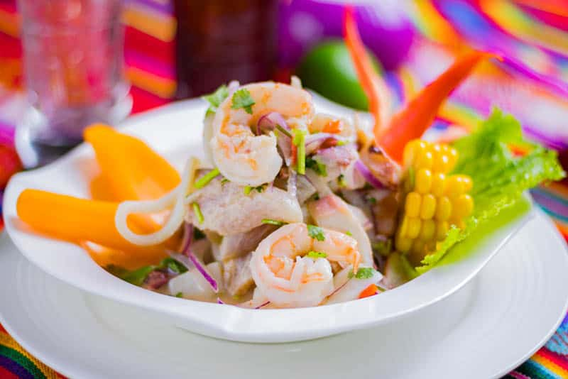 fish ceviche served with vegetables on plate