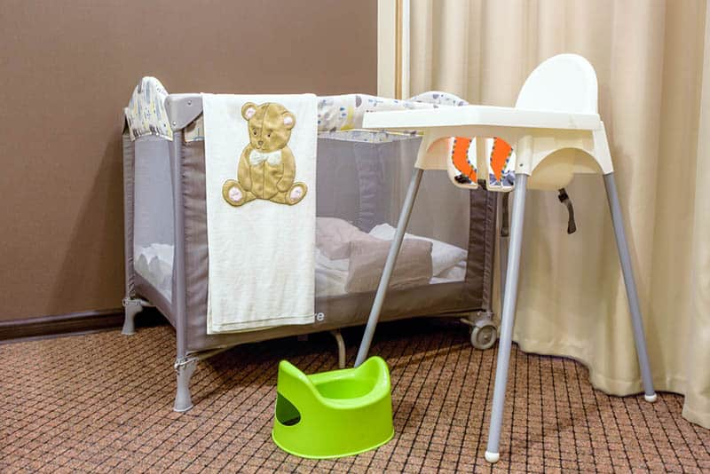 grey portable baby bed with high feeding chair and green pot in bedroom