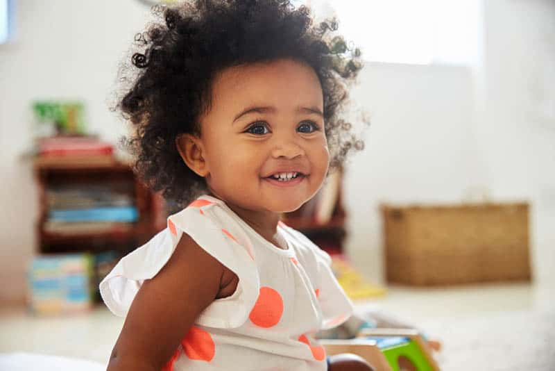 happy baby girl playing with toys on the floor