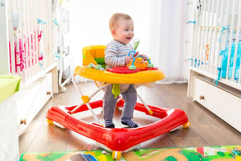 happy little baby walking at home in colorful walker