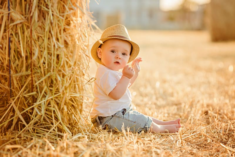 little adorable baby boy wearing hat sits in a field near haystacks at sunset