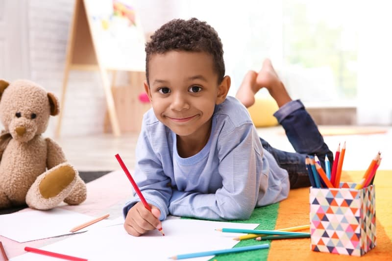 little boy drawing on the floor with a pencil