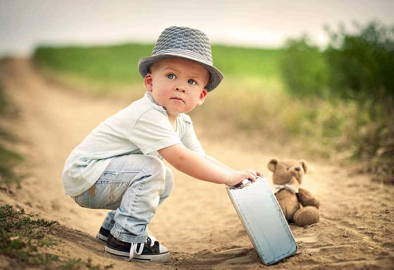 little boy holding a suitcase with teddy bear on the sand